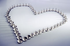 Love hurts. Heart made out of thumbtacks suggesting relationship difficulties stock photo