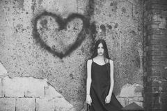 Love hurts. Girl posing with heart graffiti on grey wall. Woman wearing black dress on grunge environment. Love symbol of spray paint. Valentines day holiday stock photo