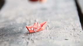 Love idea, the inscription on a paper boat. Love concept, inscription on a red paper boat, composition on vintage table stock footage