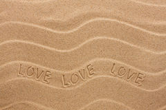 Love inscription on the wavy sand Stock Image