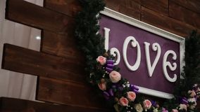Love inscription on a wooden background, flashing lights and flowers. Decorative artistic animation devoted to the. Love inscription on a wooden background stock video footage