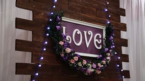 Love inscription on a wooden background, flashing lights and flowers. Decorative artistic animation devoted to the. Love inscription on a wooden background stock video