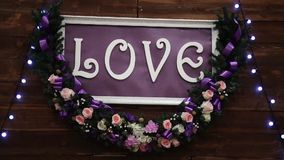Love inscription on a wooden background, flashing lights and flowers. Decorative artistic animation devoted to the stock footage