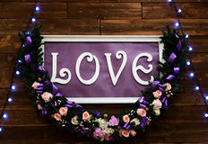 Love inscription on a wooden background, flashing lights and flowers. Decorative artistic animation devoted to the stock photo