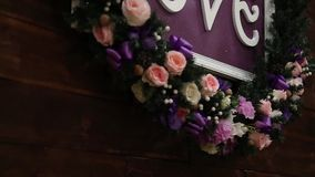 Love inscription on a wooden background, flashing lights and flowers. Decorative artistic animation devoted to the stock video footage