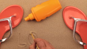 Love, inscription written by hand on the sand, among beach accessories. Sign and symbol recreation. stock video