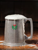 Love the Irish. A shamrock pewter mug overflowing with frothy beer Stock Images