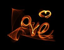 Love isolated word lettering and heart written with fire flame or smoke on black background.  Royalty Free Stock Photography