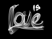 Love isolated word lettering and heart written with fire flame or smoke on black background.  Royalty Free Stock Image