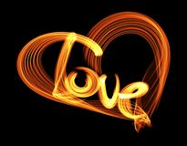 Love isolated word lettering and heart written with fire flame or smoke on black background.  Stock Photo