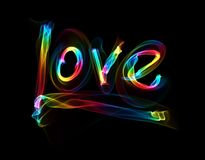 Love isolated word lettering written with rainbow fire flame or smoke on black background.  Royalty Free Stock Photos
