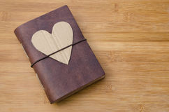 Love journal. Old notebook or diary on a wooden table with a handmade cardboard heart on top Royalty Free Stock Photography