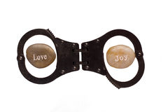 Love and Joy pebbles in hand cuffs isolated on white Stock Image