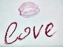 Love and kiss. Inscription love and a kiss on a white background made of red lipstick Stock Images