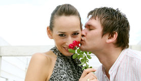 Love Kisses. A man presents a flower and kisses a girl royalty free stock image