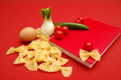 Love in the kitchen. Red cook book with colourful vegetables on red background Stock Photography