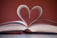 Love of knowledge. A book whose pages are folded in the shape of heart Stock Image