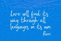 Love language Rumi. Love will find its way through all languages on its own - ancient Persian poet and philosopher Rumi quote handwritten on blue wall Stock Photography