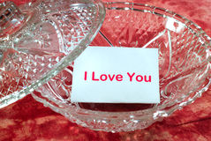 Love Letter. A love letter sitting in a glass candy dish which says, I love you Stock Photos