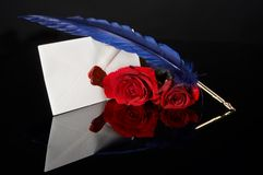 Love letter. Sealed, with two red roses and a quill feather stock photo