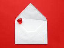 Love letter. A white envelope with paper and heart on red Stock Photography