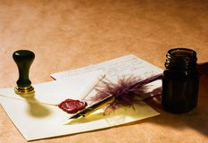 Love Letter. Still-life about a love letters with a quill, an inkwell & a stamp on a rustic paper Stock Images
