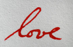 Love Letter. Close-up of a word love written in red ink on white paper royalty free stock image