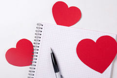 Love letter concept - note book with pen and paper hearts Stock Photos