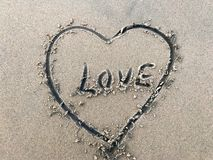 Love letter drawn in middle heart beach on sand with sea waves stock image