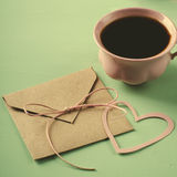 Love letter, envelope and pink cup of coffee. Valentines card. Horizontal, flat lay Royalty Free Stock Photo
