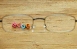 Love letter with heart shape looking passing eyeglass. On wooden board royalty free stock image