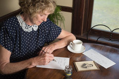 The Love Letter. In a historical scene from the 1930's or 1940's, an attractive elderly woman writes a letter as she sits at a table by a window royalty free stock photos