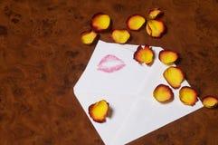 Love letter - Liebesbrief. Love letter with yellow-red rose petals on noble wooden desk - Liebesbrief mit gelb-roten Rosenblaettern auf edlem Holztisch stock photo
