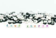 Love letter message written with colored letters and black and white letter in background on white concept photo Royalty Free Stock Photos