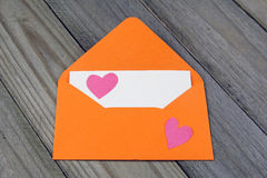 Love letter- orange envelope with paper heart on blank card Stock Photos