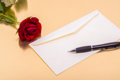 Love letter and a rose on a golden background Stock Image