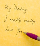 Love letters. A simple hand written message of love on parchment paper with the pen in position to finish of the message royalty free illustration