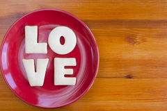 Love letters cookies on red plate. Valentine's Day or home baking for loved ones concept stock image