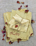 Love letters and envelopes made of antique parchment paper with dried rose petals Stock Photo