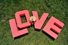 Love letters in grass. Huge red letters wedding bouquet love and are located on  green grass Stock Images