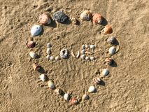 Love letters made in heart shape of Seashells on the sand beach. royalty free stock image