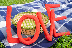 Love letters over a picnic blanket and a basket Royalty Free Stock Photos
