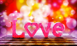 Love letters. Pink love letters on a wooden surface with a bokeh of bright colors. Stars twinkle brightly for this concept of love for Valentines day or stock photos