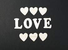 Love with letters and wooden hearts on black background. Stock Photos