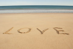 Love letters written in sand on ocean beach Royalty Free Stock Photography