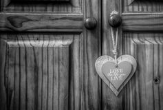 Love life live wooden heart. Love the life you live wooden heart on old rope string strap on closet wooden door stock photo
