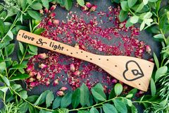 Love and Light - letters burnt in wooden handle with rosebuds and blueberry leaves stock photos