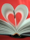 In love with literature. Book with two of its pages folded in red background Royalty Free Stock Images