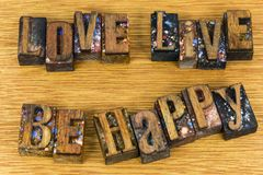 Love live be happy inspirational message. Motivational sign love live be happy success letterpress wood block grunge letters retro concept Royalty Free Stock Images