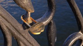 Love lock attached to fence of bridge over river. Moscow. Russia. stock video footage